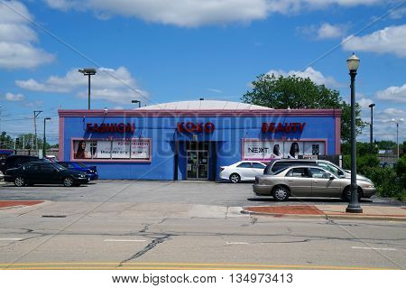 JOLIET, ILLINOIS / UNITED STATES - JUNE 1, 2015: Downtown Joliet's Koko Fashion and Beauty Supply Store features a bright blue building with pink trim.