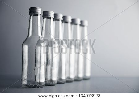 Set of unlabeled empty transparent bottles closely isolated in row line on side on simple gray background, first bottle in focus, others unfocused in bokeh