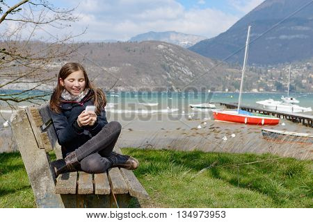 a young teenager with a phone outdoor