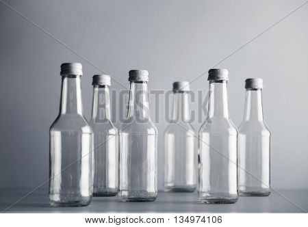 Set of empty cristal unlabeled bottles randomly presented on gray surface, isolated