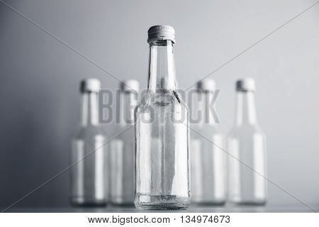 One cocktail empty glass bottle closed with white cap presented in focus in front of unfocused others