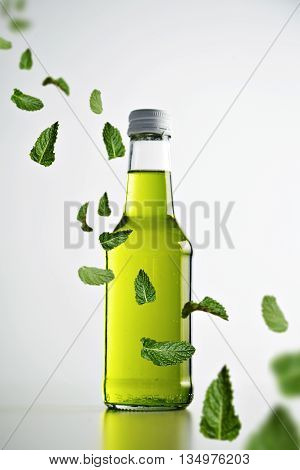 Fresh cold green lemonade in rustic sealed glass bottle isolated on white, mint leaves flying in air across, commercial retail picture