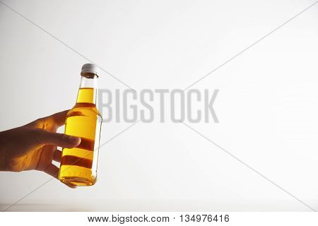 Woman hand offers cristal transparent bottle with refreshment drink inside, sealed and unlabeled. Commercial retailing photo