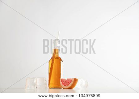 Tasty fresh aperol in transparent bottle with drinking straw near ice cubes and tangerine slice isolated on white