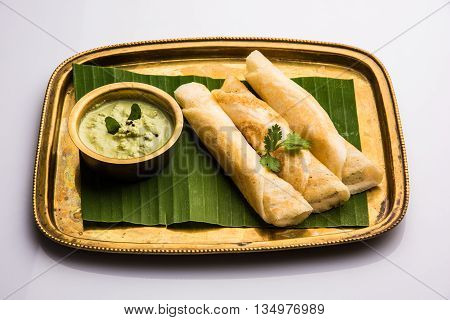 3 dosa rolls with coconut chutney in a brass tray over coconut leaf, favourite south indian meal