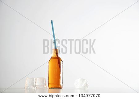 Tasty fresh cocktail in transparent bottle with blue drinking straw near ice cubes isolated on white