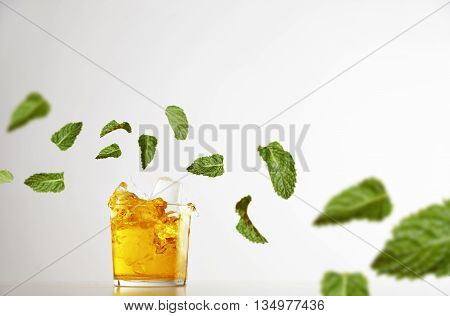 Splash fresh lemonade inside transparent glass with ice cubes isolated on white, mint leaves flying in air around, commercial