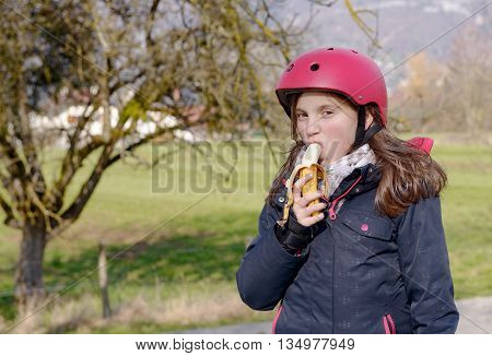 a preteen with roller skate helmet eat banana