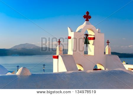 Picturesque view of church bells on a background of blue sea and sky in Oia or Ia, island Santorini, Greece