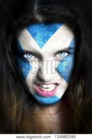 Portrait of a woman with the flag of the Scotland painted on her face.