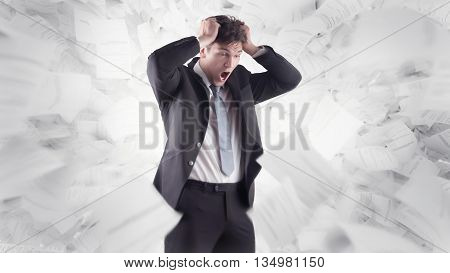 a young businessman desperately pulls his hair in the middle of numerous papers flying around