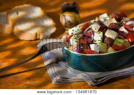 Greek salad with feta cheese tomatoes cucumber olives and onions with greek amphora and bread over a colored background