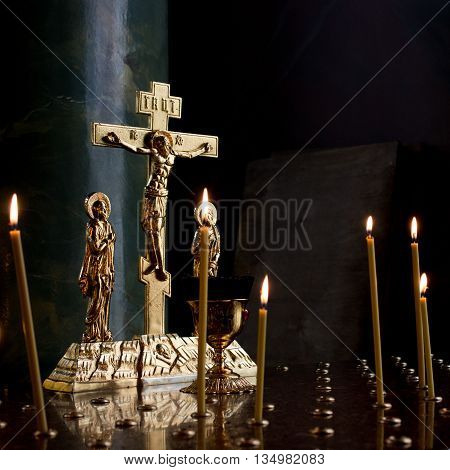 Golden crucifix with candles in a dark part of church