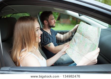 Couple of young people traveling. Couple spending weekend on nature. Searching road to go. Traveking by a car