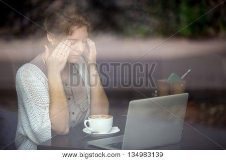 Young Woman Having Headache. Shot Through Window