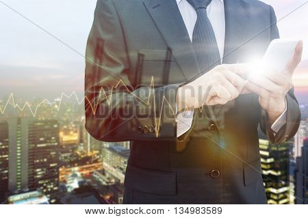 Double exposure of professional businessman using smart phone blurred city centre of business and blurred tranportation port with trading graph chart Technology & Business trading concept