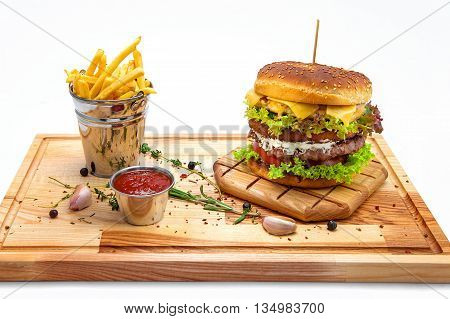 a double cheeseburger on wooden board with fries and ketchup sauce