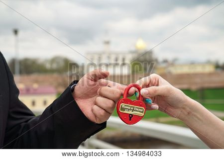 Red wedding lock with the words of Vita and Dima 30.04.2016 in the hands of the bride and groom. Wedding theme, symbol of love, newlyweds