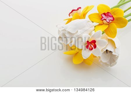 Beautiful handmade art clay narcissus and tulip flowers. Closeup over white background.