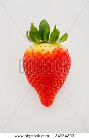 Closeup of not fully ripe strawberry. Over white background