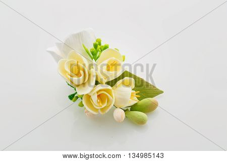 Beautiful handmade art clay spring flower bouquet. Bridal accessory. Boutonniere. Over white background.