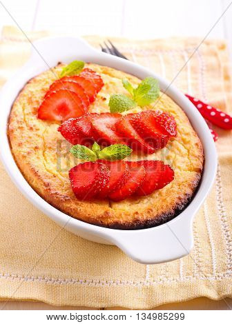 Ricotta cheese souffle in a tin with strawberry garnish