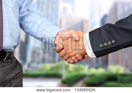 The Close-up image of a firm handshake between two colleagues outside