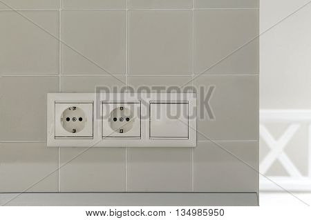 two white electric outlet and switch on the white wall tiles