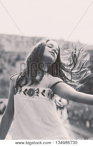 teen girl portrait with hair in motion black and white outdoor shot small amount of grain added