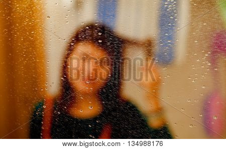 misty reflection of girl in the mirror with water droplets. combing her hair