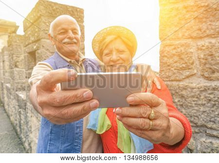 Senior couple taking a selfie at castle outdoor with back lighting - Two persons in the 60's having fun - Concept of active elderly and fun around the world with new technologies - Focus on hands