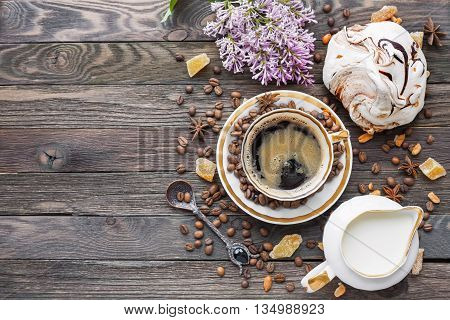 Rustic wooden background with cup of coffee milk chocolate meringue and lilac flowers. White vintage dinnerware and spoon. Breakfast at summer morning. Top view place for text.