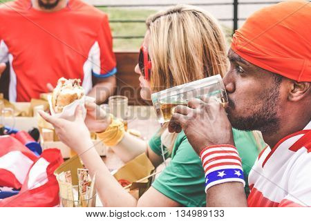 Multiracial american fans eating burgers and toasting beers in bar restaurant outdoor - Young multi ethnic supporters relaxing before sport game - Vintage retro desaturated filter