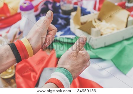 Group of football fans celebrate and support their national team - Two sport supporter from different team eating together - European football fans concept - Focus on bottom hand - Vintage editing