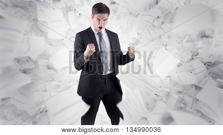 a young businessman clenches his fist in the middle of numerous documents flying around
