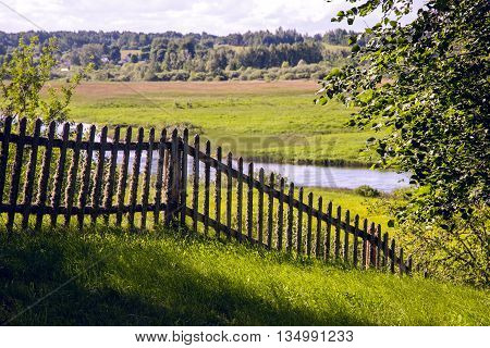 old wooden fence in summer Sunny day, covered with moss from time to time