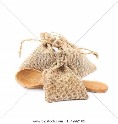 Tiny sackcloth bag with a tie string next to a wooden spoon, composition isolated over the white background