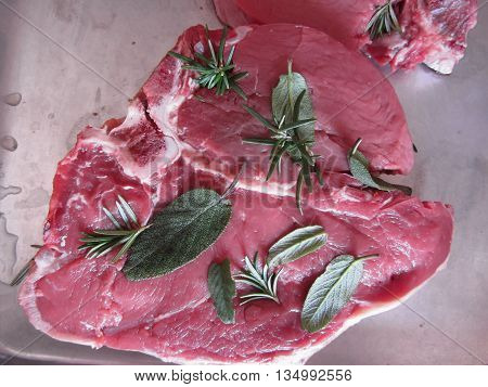 Fresh raw marbled meat steak with sage and rosemary ready to be cooked in the oven