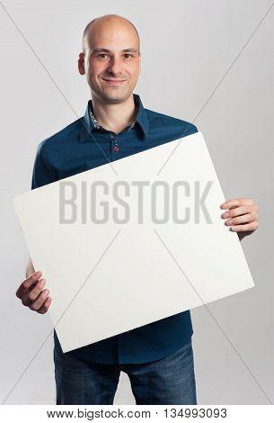 Handsome Smiling Bald Man Presenting Empty Paper Sheet
