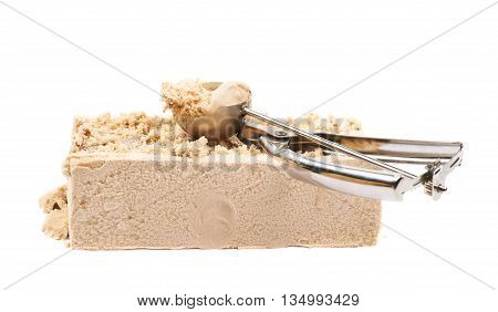 Briquette of a caramel ice cream with a special steel spoon over it, composition isolated over the white background