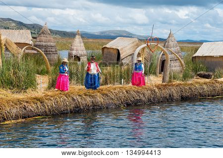 TITICACA PERU MARCH19 2015 - Local people in traditional attires welcome tourists coming by boats at Uros islands on Lake Titicaca.