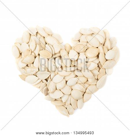 Heart shape made of pumpkin seeds isolated over the white background