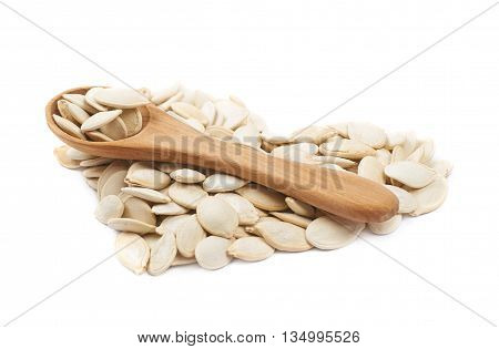 Heart shape made of pumpkin seeds and the wooden spoon over it, composition isolated over the white background