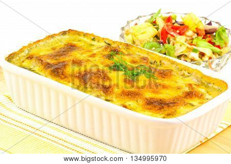 Salmon gratin and salad on a white background