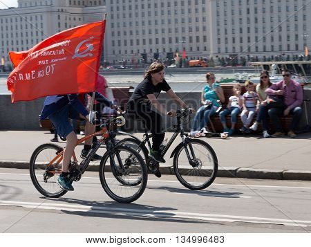 Moscow - May 9 2016: People - Patriots bikes carry the red flag of victory in the Victory Day May 9 2016 Moscow Russia