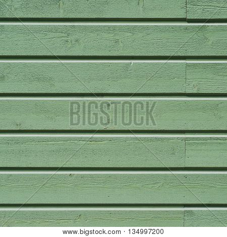 Close-up fragment of a wall made of an old green painted wooden planks as a background texture composition