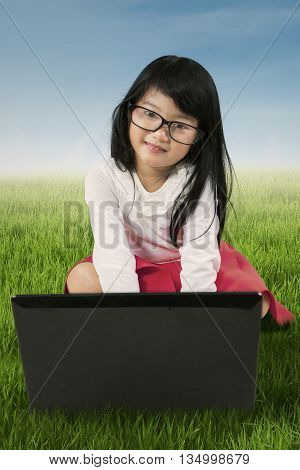 Adorable little girl sitting on the grass while wearing glasses and using laptop computer