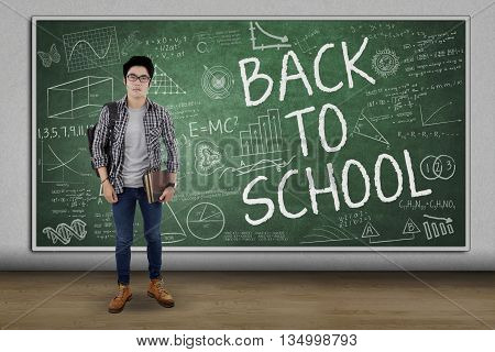 Male high school student standing in the classroom while carrying book and bag with text of Back To School on the chalkboard