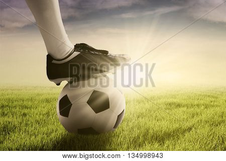 Picture of a soccer ball and foot of football player on the green meadow shot at sunrise time