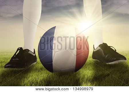Soccer ball with national flag of France and foot of football player on the meadow